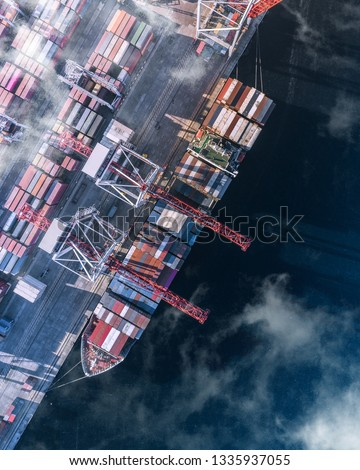 Top view of a cargo ship with containers, which is unloaded in the port. Container Warehouse, Logistics, Cranes, Outdoor, Import and export. Top view #1335937055