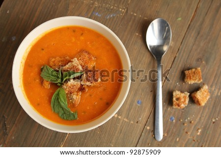 Top view of a carrot soup with spoon and bread