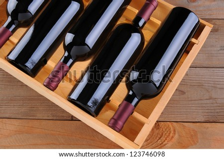 Top view of a case of cabernet sauvignon wine bottles. Horizontal format with a rustic wood background.