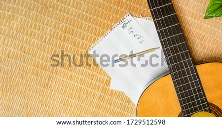 Top view of a classical guitar, music notebook with stave and pencil with big copy space left. Concept of composing or studying music. Foto stock ©