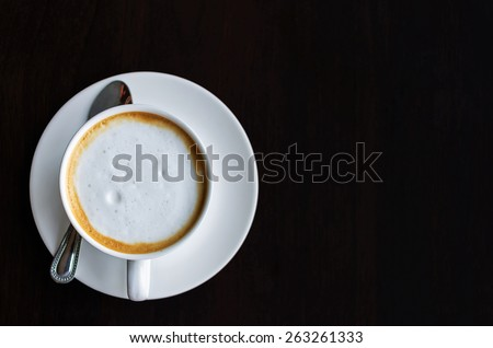 Top view of a cup of coffee, cappuccino on a wooden table.