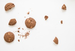 Top view of a cup of coffee with chocolate cookie on white background.