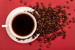 top view of a cup of coffee with coffee beans isolated on a res background