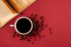 top view of a cup of delicious coffee with coffee beans isolated on a res background with copy space