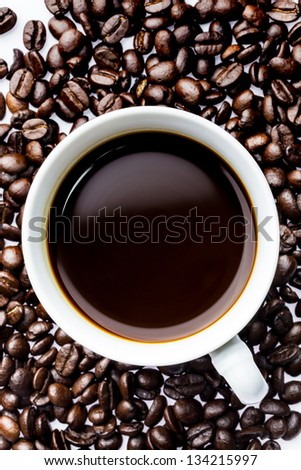 Top view of a cup of hot coffee on coffee beans background