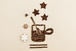 Top view of a cup or mug of coffee lined with roasted coffee beans with a bronze spoon inside on a light paper background. Different types of stars: with brown coffee beans, anise and gingerbread