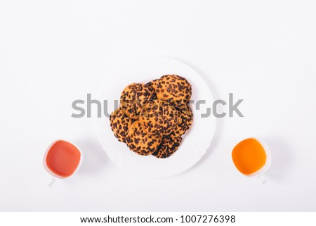 Top view of a cup with fruit juice and cookies on a white table #1007276398