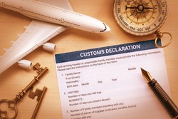 Top view of a customs declaration form with a white model air plane, a fountain pen on a table. Customs declaration form is a form declaring the nature and value of goods, etc. for customs purposes.