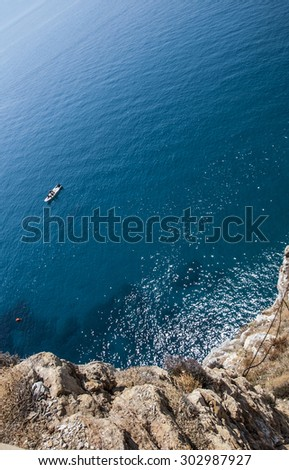 Top view of a deep blue sea and rocks of the coast. A little boat sailing
