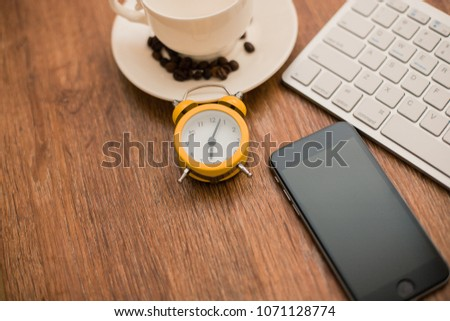 Top view of a desk designer with a laptop, tablet, gadget for mobile phone, alarm clock, coffee cup, wooden background.