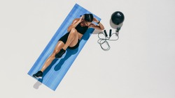 Top view of a female athlete doing abdomen exercises. Woman in fitness wear training doing abdomen crunches with a medicine ball and skipping rope by her side.