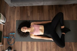 Top view of a fit young woman practicing yoga in the living room and doing a bound angle pose