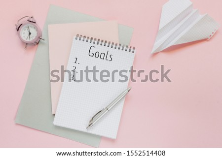 Top view of a flat lay of desktop and notepads for writing down goals and plans. 2020 New Year's goal, plan, action text on notepad with office accessories. Business motivation, inspiration concept.