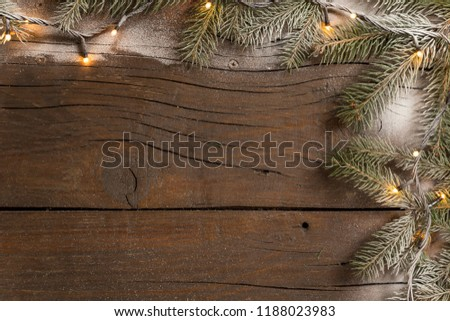 Top view of a frame made of snowy pine branches and Christmas lights placed on wooden table #1188023983
