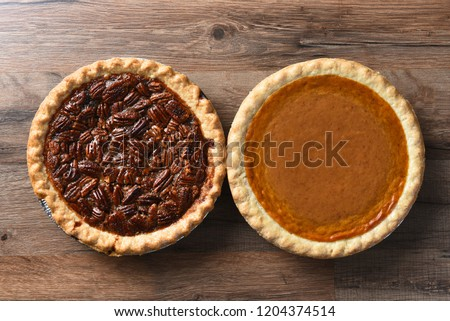 Top View of a fresh baked pumpkin pie and a pecan pie on a rustic wood table, for Thanksgiving feast. #1204374514