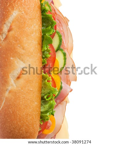 Top view of a fresh submarine sandwich with lettuce, cheese, turkey, ham, yellow peppers, cucumbers and tomatoes
