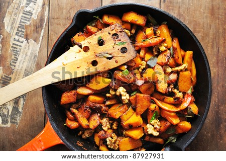 Top view of a freshly cooked skillet full of balsamic vinegar glazed pumpkin with walnuts and chili - stock photo