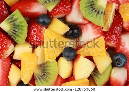 Top view of a fruit salad with strawberries, oranges, kiwi, blueberries and peaches