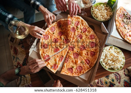 Top view of a group of friends eating big pizza and drinking white vine while having a home party