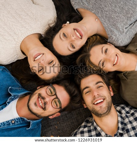 Top view of a group of friends lying on floor and looking at camera #1226931019