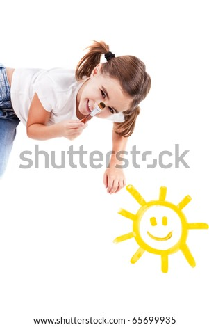 Top view of a happy girl lying on floor and painting a happy sun