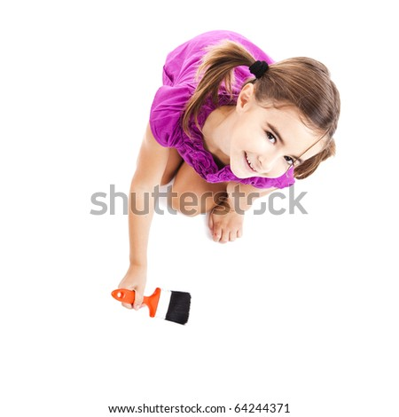 Top view of a happy girl sitting on floor holding a paint-brush