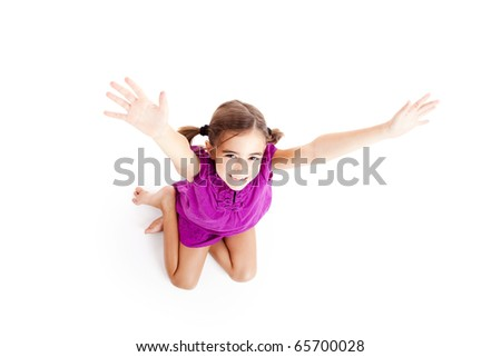 Top view of a happy girl sitting on floor with arms open