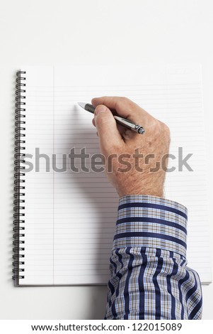 Top view of a human hand writing on book.