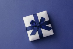 Top view of a little gift box with ribbon. Blue backdrop with space for your text
