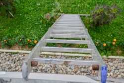 Top view of a long silver aluminum ladder leaning against the wall of the house. Close up view from top of tall step ladder at roof. work at height. Ladder for workers, painters, engineers, repairman