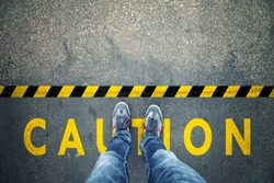 Top view of a man stands on industrial striped asphalt floor with warning yellow black caution pattern.