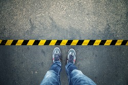 Top view of a man stands on industrial striped asphalt floor with warning yellow black pattern.