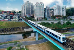 Top view of a metro train of Wenhu MRT Line traveling on a bridge & residential buildings standing by a little river in the suburban area on a beautiful sunny day in Taipei, the capital city of Taiwan
