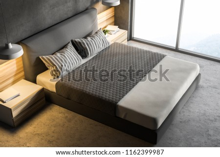 Top view of a modern bedroom with gray walls, a concrete floor, a double bed and two bedside tables with lamps. Loft window with a scenery. 3d rendering mock up