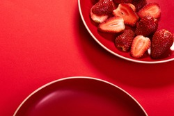 top view of a monochromatic composition or flat lay with sliced strawberries served on a ceramic plate on red background