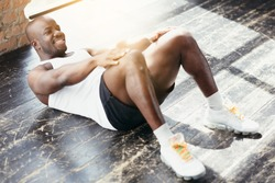 Top view of a muscular dark-skinned Pilates trainer doing abdominal and abdominal exercises