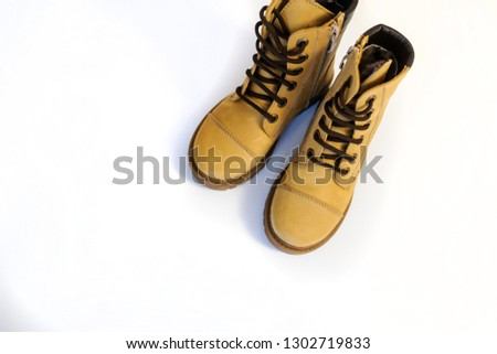 top view of a pair of yellow leather child shoes on a white background #1302719833