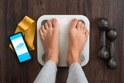 Top View Of a Person Standing On a Smart Weighing Scale, a smartphone connected to the Scale and Fitness equipment. Smart technology and health care concept