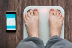 Top View Of a Person Standing On a Smart Weighing Scale and a smartphone connected to the Weighing Scale laying nearby