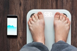 Top View Of a Person Standing On a Smart Weighing Scale and a smartphone connected to the Weighing Scale. Smart technology concept