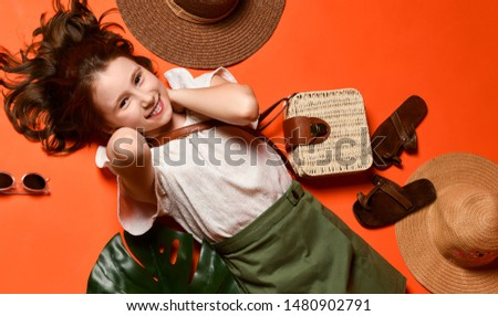 top view of a pretty undergrow girl in a business T-shirt and khaki skirts on a terracotta background gets pleasure and pleasure to lie down to rest. Boho accessories.