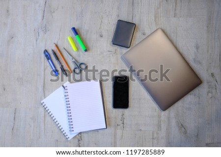Top view of a project using laptop, hard drive, smartphone, notebooks and writing implements.  Flat lay of   educational and work equipment set on a light grey wooden surface.