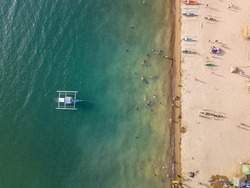 Top view of a public beach, with a sole outrigger boat in the shallow water. Tourist spot in Calayo, Nasugbu