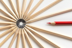 Top view of a red pencil tends to fall into a circle of gray pencils lying on a white background. Concept of unsuitable standout employee in an office team. Eccentric concept