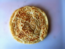Top view of a roti prata, Indian-influenced flatbread, is a well-known dish in Southeast Asian countries.