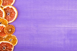 top view of a row of dried orange and grapefruit slices arranged on the side on purple wooden background with copy space