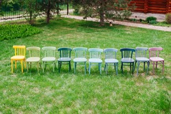 top view of a row of wooden Viennese chairs painted in cheerful bright colors in the backyard, eco-friendly workshop for the restoration of old furniture.