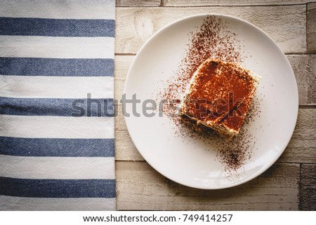 Top view of a slice of homemade tiramisu (traditional Italian dessert) on a white plate on a wooden board with a white and blue kitchen cloth. Landscape format.