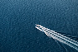 Top view of a small boat floating in the sea and creates a white waves. Amazing view to Yacht sailing in open sea at windy day