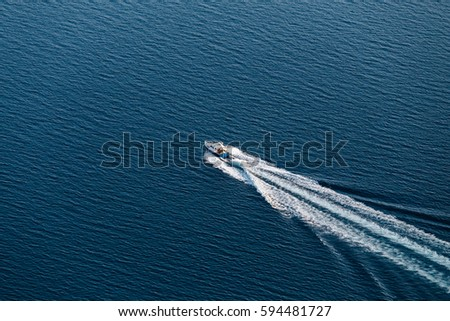 Top view of a small boat floating in the sea and creates a white waves. Amazing view to Yacht sailing in open sea at windy day #594481727